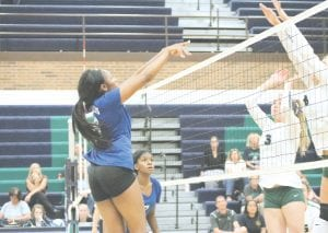 Carman-Ainsworth's Diamond Lester rises above the net for a spike against Lapeer on Sept. 11. Photo by Kylee Richardson