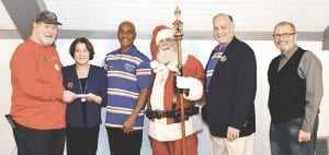 From left, Chris Hamilton, Executive Director of the Old Newsboys of Flint, receives a check from Janice Buchanan of the Gleason Community Fund. Continuing left are: Calvin McQueen of the Gleason Community Fund, Santa Claus, John Gleason, director of the Gleason Community Fund, and Gary Gould, a Gleason board member. Photo by Gary Nickel