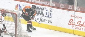 SCF's Cody Harburn fires the puck along the boards while battling Grand Blanc last year. Photo by Brandon Pope