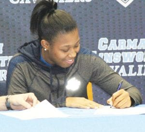 Carman-Ainsworth's Destiny Strother smiles as she signs her letter of intent last Wednesday at Carman-Ainsworth High. Photo by Brandon Pope