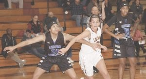 Carman-Ainsworth's Aaliyah McQueen (21) battles at the boards against Davison's Anna Tomczak. Photo by Lisa Paine