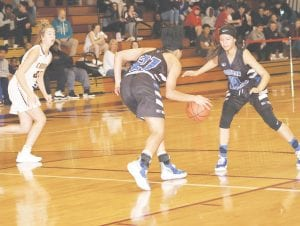 Carman-Ainsworth's Aaliyah McQueen (21) breaks away on the steal as Rayven Brantley backs her up at Davison at Dec. 11. Photo by Lisa Paine