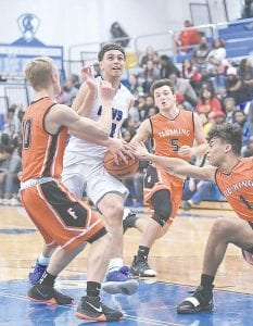Carman-Ainsworth's Dustin Fletcher absorbs contact as he drives the lane during Friday's win over Flushing. Photo by Todd Boone
