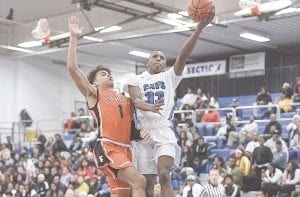 Carman-Ainsworth's James Robinson takes it to the hole against Flushing on Jan. 4. Photo by Todd Boone
