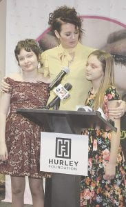 At left, Lauren Stansburry stands with Melissa and Hannah Schummer as the next version of McKenna's legacy is unveiled in a portable, outpatient beauty box for Hurley patients.