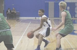 Mehki Ellison helps keep Carman-Ainsworth's win streak alive, as he looks for an open teammate in Feb. 8's victory over Lapeer. Photo by Brandon Pope