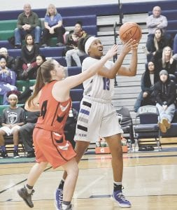 Carman-Ainsworth's Destiny Strother beats Grand Blanc's Katherine Mansour to the basket in the Div. 1 district opener at Lapeer Monday. Photo by Terry Lyons