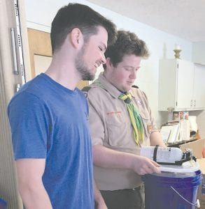 At left, Jacob Sanborn another Eagle Scout of Troop 106, works with Mason Coon work on preparing the buckets. Photo provided