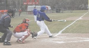 Carman-Ainsworth's Kyle Resterhouse puts the bat on the ball at Swartz Creek on Apr. 10. Photo by Brandon Pope