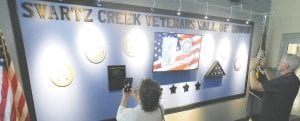 Visitors photograph the scrolling display honoring local veterans at the Cage Community Center. Photos by Lania Rocha
