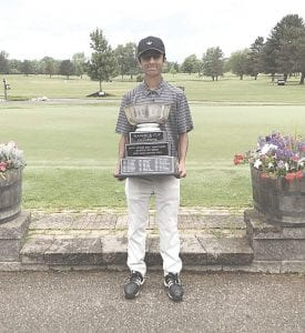 Grand Blanc's Ranveer Ajimal holds the coveted Mancour Cup that he won Tuesday.