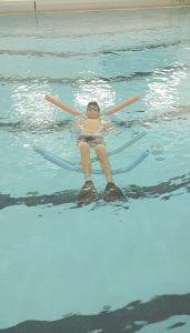 A young patron enjoys open swim at the Carman-Ainsworth High School pool. Photo via Carman-Ainsworth Athletics Twitter
