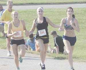 Friends hold hands as they compete in the Kayla O'Mara Memorial Road Race in 2012. File Photo