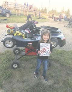 Alissa Wilson shows off her custom fabricated go-kart and the sign her friend made for her at Owosso Motorsports Park. Alissa, who turns 10 on Friday, has been racing all summer.