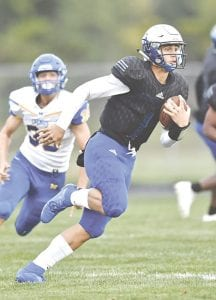 Carman-Ainsworth quarterback Dustin Fletcher heads up field against Midland last Friday. Photo by Don Brovont