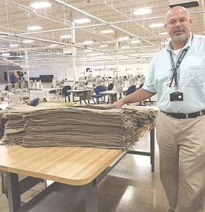 Plant Manager Larry Stevens explains the process for sewing the winter weather undergarments created at Peckham for the U.S. Armed Forces.