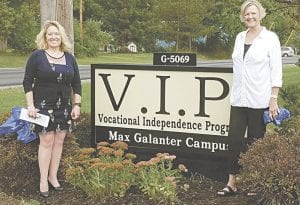From left, Rene McMann, Executive Director and Jeanne Quinlan, Board Secretary, with the new sign in front of the Vocational Independence Program.