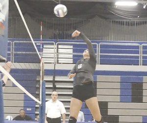 Carman-Ainsworth's Emily Carroll spikes the ball over the net on Sept. 12. Photo by Jolette Rossi