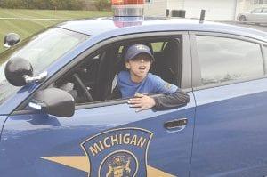 Johnny Porter posing with police cruiser Photos by Ben Gagnon
