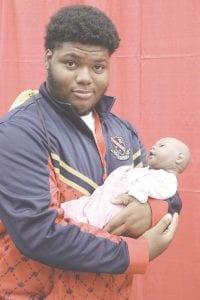 Burton's Bendle Public Schools student Dominick Spearman checks out a mock infant found at a display by Mott Community College's Nursing Program.