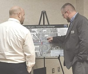 Keith Brown, left, and Craig Innes, both with the Michigan Department of Transportation Davison Transportation Service Center, look over a drawing of the proposed reconstruction of the Corunna Road interchange during a public input meeting Dec. 11 at the Flint Township Police Department. Photo by Jalene Jameson