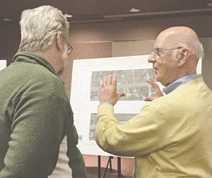 """Genesee County Road Commission engineer Richard Hill, left, and GCRC Chairman John Mandelaris, right, discuss the proposed plan to resurface Van Slyke Road from a four-lane roadway to a three-lane roadway with a center left-turn lane from Maple Avenue to Bristol Road. Hill and GCRC engineer Bonnie Wood presented information on the """"road diet"""" at a public meeting Dec. 12 at the Flint Township Police Department. Photo by Jalene Jameson"""