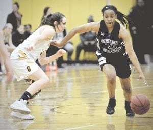 Carman-Ainsworth's Chenelle King drives hard past Goodrich's Emily Bescoe at the Steve Schmidt Roundball Classic at Mott Community College Friday. Photo by Terry Lyons