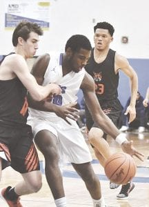Carman-Ainsworth's Isaiah Jones protects the ball from a Grand Blanc defender earlier this season. Photo by Terry Lyons