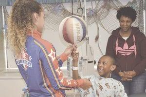 Hoops Green shows Elijah Smith, age 6, how to spin a basketball on his fingertip. Photos by Ben Gagnon