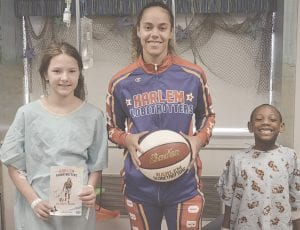 Hoops Green poses with Hurley patients Natalie Burrows (left) and Elijah Smith (right).