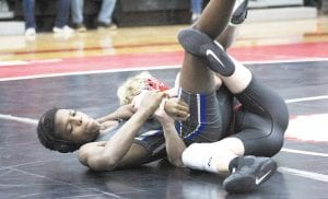 Jabril Muhammad of Carman-Ainsworth works against a Grand Blanc opponent during a meet at Grand Blanc on December 18. Photo by Joe Oster