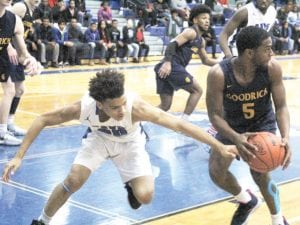 Carman-Ainsworth's Mehki Ellison goes for a steal against Goodrich's JaCoby Brandon during the second half of the Cavaliers' win on Jan. 21. Photo by Joe Oster