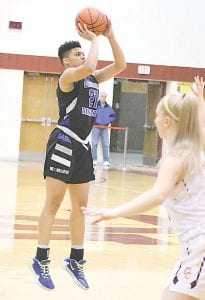 Carman-Ainsworth's Aaliyah McQueen launches a three-pointer against Davison on Feb. 4. Photo by Kylee Richardson