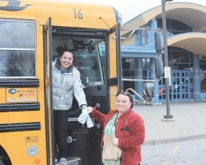 Lisbeth Gatica (left), a Carman-Ainsworth employee hands out meals for the children of Melissa Edmiston who attend Dye Elementary. Photo by Paula K. Schmidt