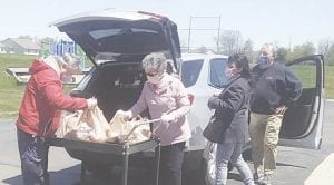 Volunteers Richard Moreland, Barb Young, and Suzette Ehrhart unload donations.
