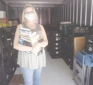 Jessica Jewell, Swartz Creek Middle School librarian, selects some titles from more than 200 crates full of books in the Friends of the Perkins Library's storage unit. The Friends donated hundreds of books to school last week. Photo by Lania Rocha