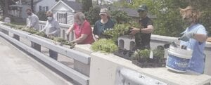 Volunteers Steve Long, Deborah Kirby, Kathy Smith, Tammy Parenteau, George Hicks and Rae Lynn Hicks were part of a 14-person crew that spent Saturday morning beautifying downtown Swartz Creek. Photo by Lania Rocha