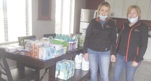 Lynn Mattila, team leader for the Grand Blanc and Fenton Keller Williams real estate offices, and Julie Moen, agent, spent their Saturday afternoon collecting and sorting donations for flood victims in Midland County. Photo by Lania Rocha