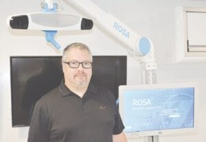 Dr. Paul Telehowski with ROSA's monitor component. Photos by Ben Gagnon