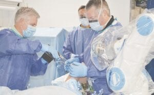 Dr. Telehowski (right) participates in a training session with the ROSA system.