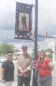 Abby Baker, president of History of Hometown Heroes, U.S. Army veteran Tom Toohey, and Grand Blanc City Manager Wendy Jean- Buhrer rolled out the city's veteran banner program Wednesday, June 24. Photo by Lania Rocha
