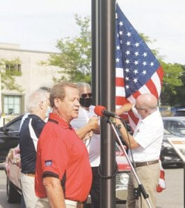 Members of the Board of Directors for Back to the Bricks, along with its founder, Al Hatch, raise the first American flag to fly on the new flagpole.