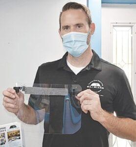 Brian Bowden displays a faceshield manufactured at BAJ Glass. Photos by Ben Gagnon
