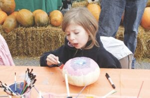 This young girl tries her hand at painting a pumpkin during the 2019 Davison Pumpkin Festival. File photo