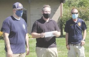 Burton Firefighters Josh Mather, left, and Doug Hedrick, far right, present Kris Johns (center) with an envelope containing the $500 the fire department raised for the Burton Dog Park project.