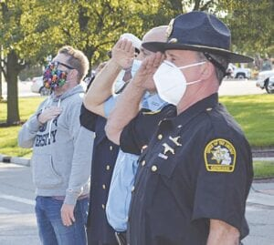 Officers and spectators saluting during the national anthem. Photo by Ben Gagnon