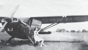Mrs. Ross Seely beside one of the planes at her husband's airfield near Belsay and Lapeer roads in Burton. Photo courtesy of the Burton Area Historical Society