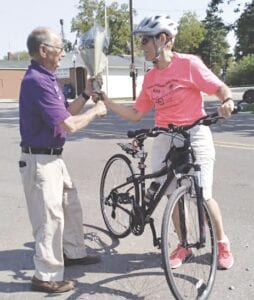 Lions District 11 D-1 Governor Harold DeMott, past president of the Gaines Lions Club, presents bicyclist Debra VanTol with a bouquet of flowers upon her arrival in Gaines on Friday. Photo by Lania Rocha