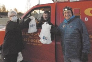 Donna Bullard, Security Credit Union and Burton Chamber of Commerce, and Steve Welch, Burton Chamber of Commerce and Burton Kiwanis hand out a volunteer bag to one of the technicians before heading out. Photo by Pete Clinton