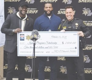 Former U of M football stars Devin Gardner (left) and Braylon Edwards (middle) presenting the check to Genesee County Sheriff Chris Swanson. Photo by Ben Gagnon